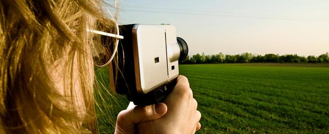 Kamerafrau vor grüner Wiese.
